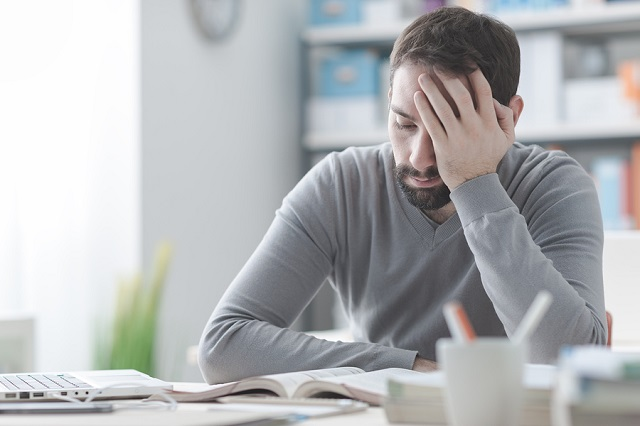 bigstock Exhausted Man With Headache 138447629