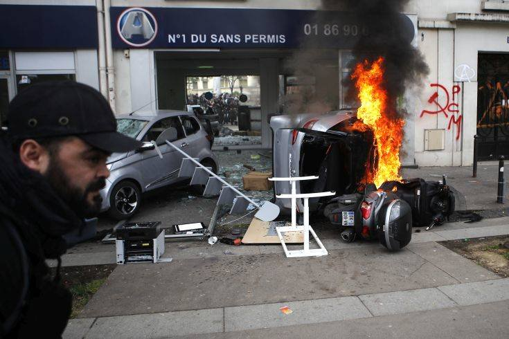 A man runs past a burning car and scooter set on fire by activists activists during the traditional May Day rally in the center of Paris, France, Tuesday, May 1, 2018. Each year, people around the world take to the streets to mark International Workers' Day, or May Day. (AP Photo/Francois Mori)