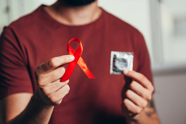 bigstock Man Holding Condom And Red Rib 331649992